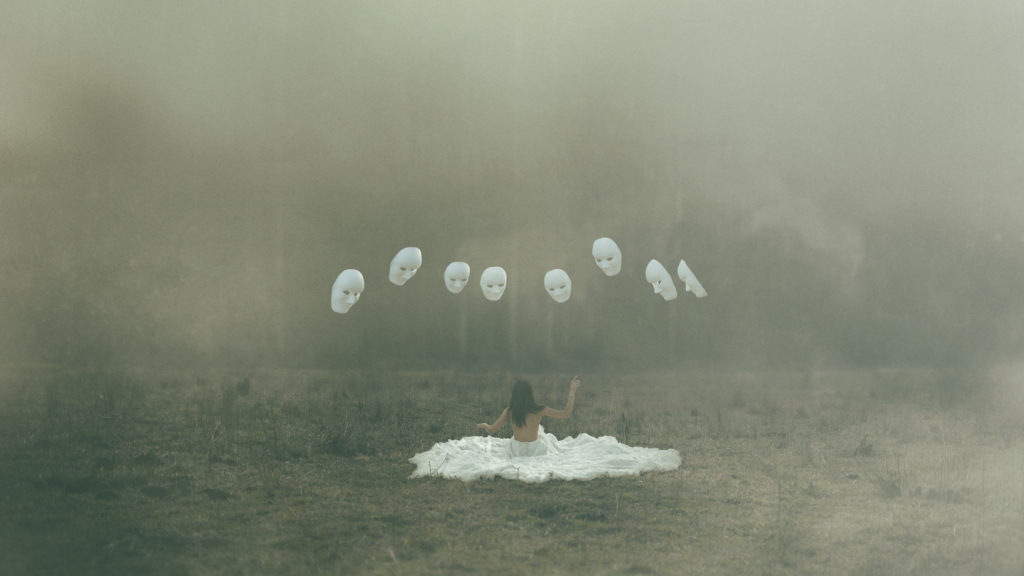 girl in field surrounded by masks
